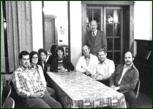A group of credit union board members in the 70s gather around a table for a photo